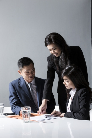 Three Chinese Business people meeting in office to discuss a project photo
