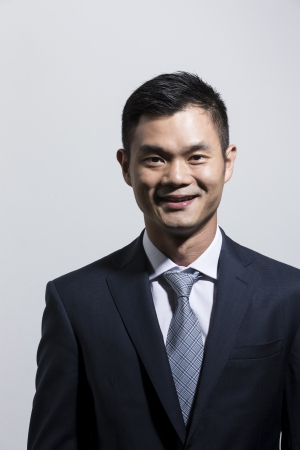 Portrait of a young Chinese business man. Grey background. photo
