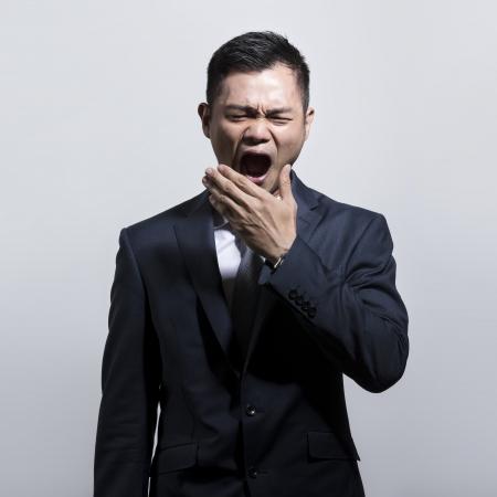Fatigué et surmené homme d'affaires chinois béant.
