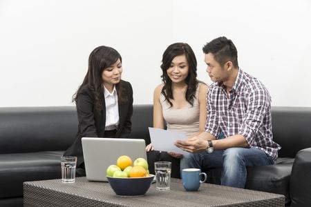 Sales Consultant montrant de nouveaux plans d'investissement pour jeune couple chinois
