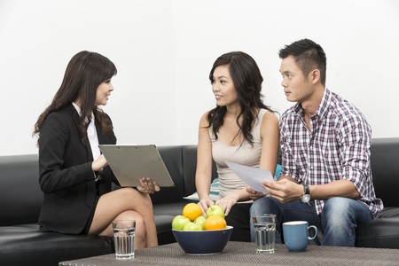 Sales Consultant showing new investment plans to young Chinese couple