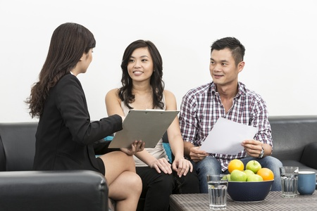 good investment: Sales Consultant showing new investment plans to young Chinese couple