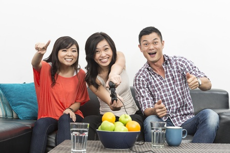 game room: Group of Young Chinese friends playing video games at home  Stock Photo