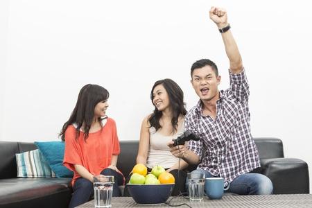 jugando videojuegos: Grupo de amigos jovenes chinos jugando videojuegos en el hogar Foto de archivo