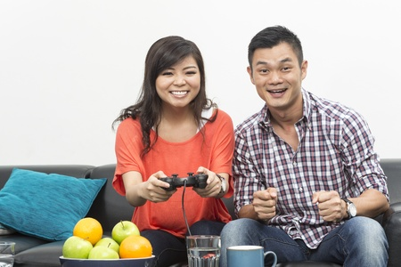 Young Chinese couple playing video games at home together Stock Photo - 20057809