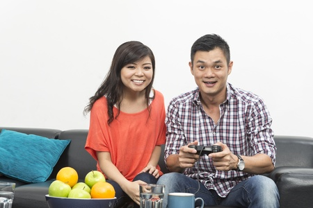 Young Chinese couple playing video games at home together Stock Photo - 20057982