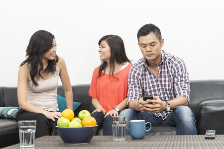 social behaviour: Group of Chinese friends hanging out together, one man ignoring group and using his phone