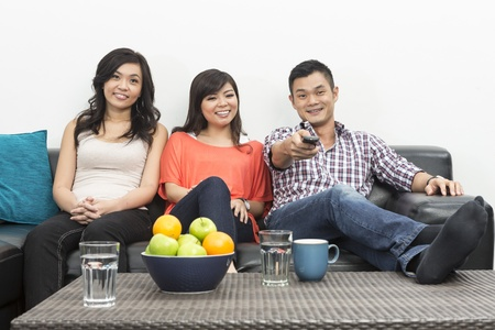 Group of Happy Chinese friends hanging out together at home watching TV photo