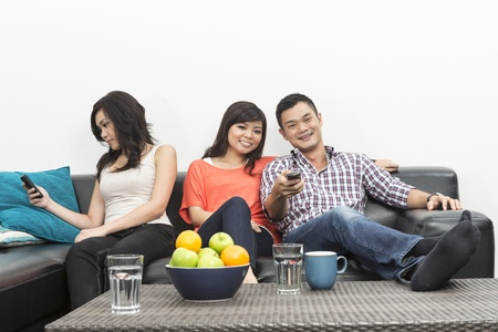 social behaviour: Group of Chinese friends hanging out together, one woman ignoring group and using her phone