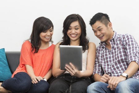 Group of Happy Chinese friends hanging out together at home using Digital Tablet photo