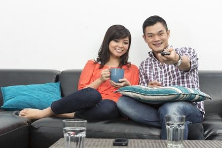 pareja viendo television: Yound y feliz pareja de chinos salir juntos en casa viendo la TV