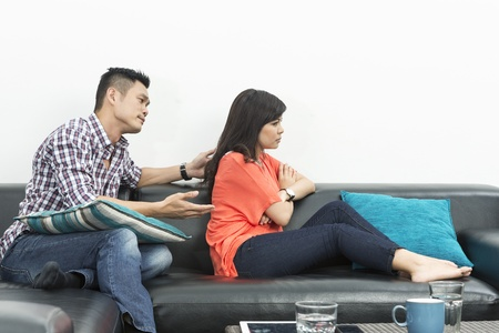 angry couple: Angry Chinese couple having an argument in their living room Stock Photo