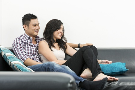 Yound and happy Chinese couple hanging out together at home photo