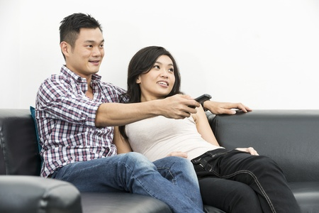 Yound and happy Chinese couple hanging out together at home watching TV photo