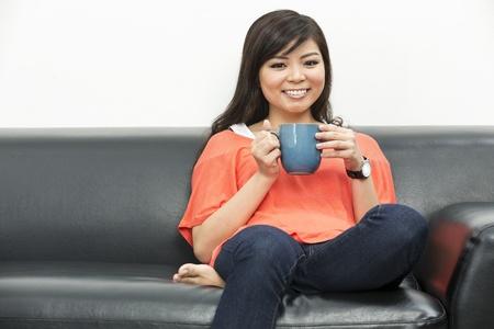 mujer china: Joven y bella mujer china en casa sentado en el sof�