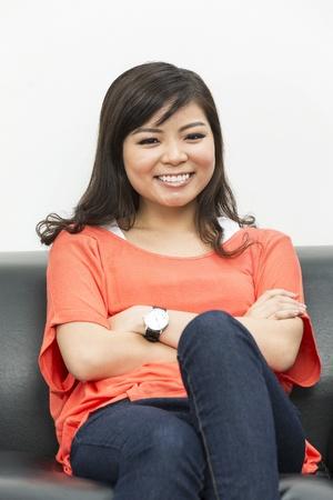 mujer china: Joven y bella mujer china en casa sentado en el sof?