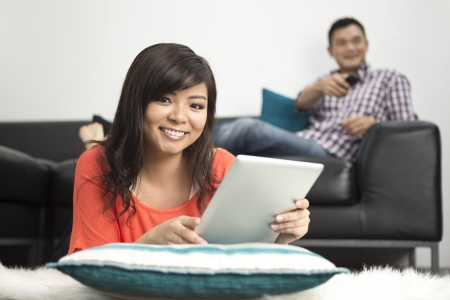 Portrait of a happy Chinese woman lying on lounge floor using Digital Tablet Stock Photo - 20058070