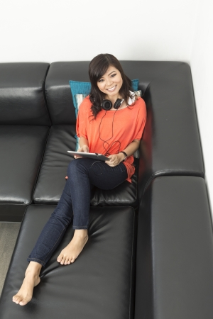 Portrait of a happy Chinese woman sitting on sofa using Digital Tablet and looking up a the camera photo