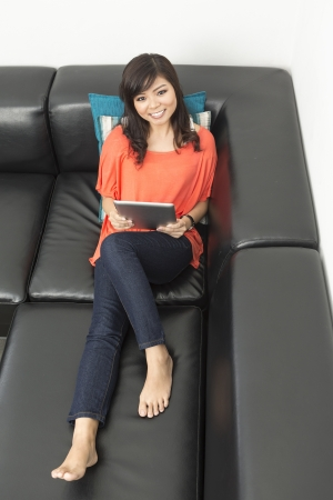 Portrait of a happy Chinese woman sitting on sofa using Digital Tablet and looking up at the camera photo