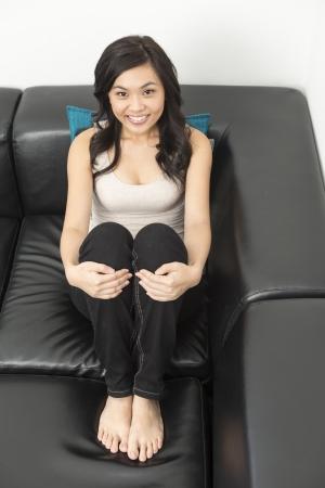 mujer china: Mujer bastante china que se relaja en casa en el sof? y mirando a la c?mara