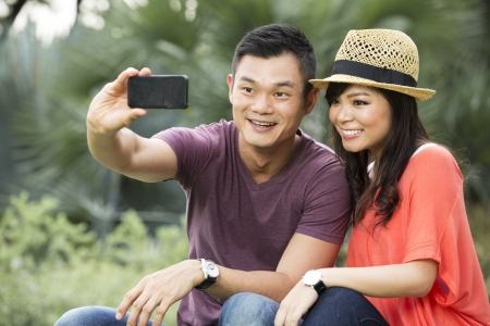 Chinese Couple taking a picture of themselves with smartphone photo
