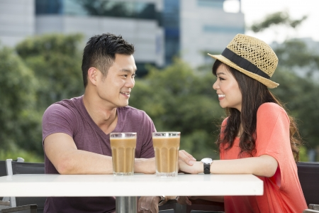 happy asian couple: Romantic Young Chinese Couple Enjoying a Coffee out together. Stock Photo