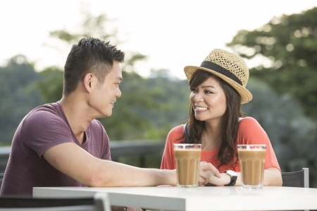 Romantic Young Chinese Couple Enjoying a Coffee out together. photo