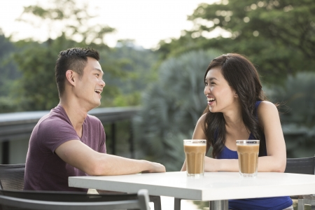 enjoying: Romantic Young Chinese Couple Enjoying a Coffee out together. Stock Photo