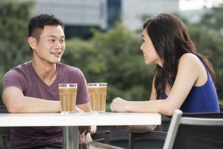 chinese drinks: Romantic Young Chinese Couple Enjoying a Coffee out together. Stock Photo