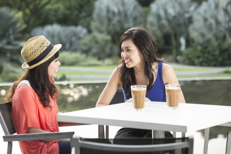 two friends talking: Two Chinese female friends Enjoying Cup Of Coffee