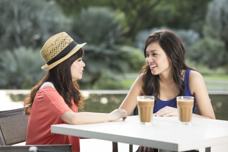 Two Chinese female friends Enjoying Cup Of Coffee