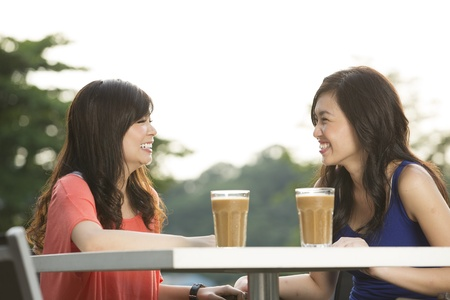 two people talking: Two Chinese female friends Enjoying Cup Of Coffee