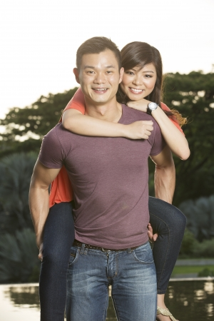 Portrait of a Chinese man piggybacking his girlfriend on a date photo