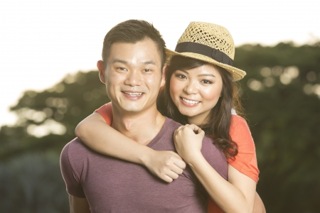 Closeup Portrait of a happy Chinese boyfriend hugging his beautiful girlfriend.  photo