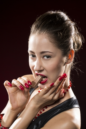 Portrait of glamourous fashion model eating chocolate. Concept about temptation and desire photo