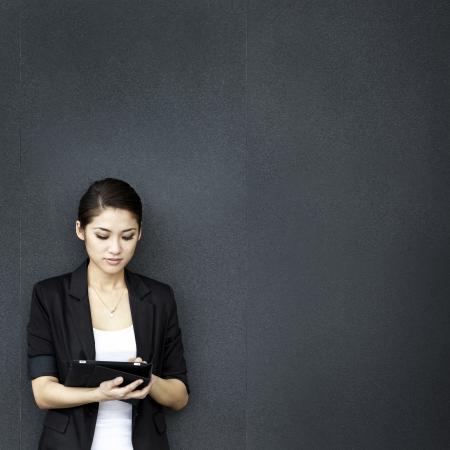 검은 벽에 기대어 디지털 태블릿 컴퓨터를 사용하는 아시아 비즈니스 여자.