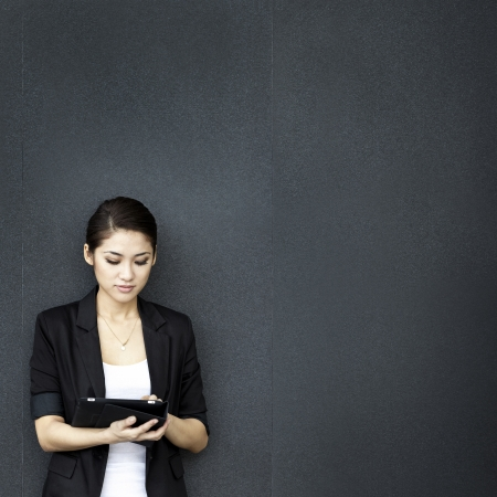 Asian business woman using digital tablet computer, leaning against a black wall. photo