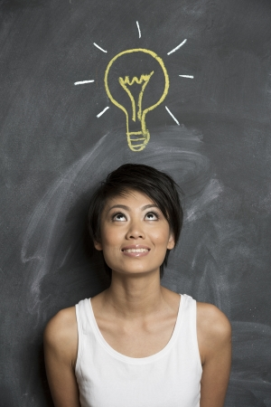 pan asian: Happy Asian woman standing in front of chalkboard with light bulb drawn above her head  Concept about ideas  Stock Photo
