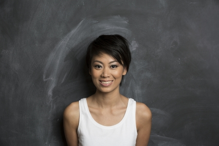 pan asian: Happy Asian woman standing in front of a dark chalkboard  The chalk board is blank waiting for a message  Stock Photo