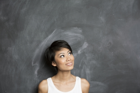 adult learning: Happy Asian woman standing in front of a dark chalkboard  The chalk board is blank waiting for a message  Stock Photo