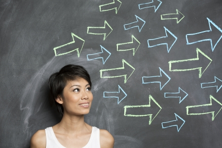 Happy Asian woman standing in front of a dark chalkboard with arrow signs drawn pointing   Stock Photo