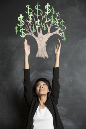 wealth management: Asian Business woman reaching for chalk money tree drawing on blackboard  Stock Photo