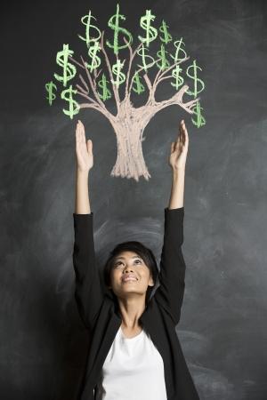 Femme d'affaires asiatique atteignant pour la craie dessin de l'arbre de l'argent sur tableau noir