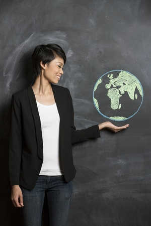 Femme d'affaires asiatique ou un enseignant avec le globe de la craie sur le tableau noir tir?es