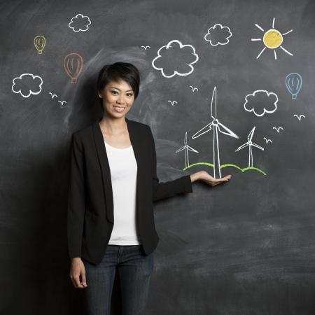 educacion ambiental: Mujer asi?tica de pie delante de boceto entorno ecol?gico en la pizarra