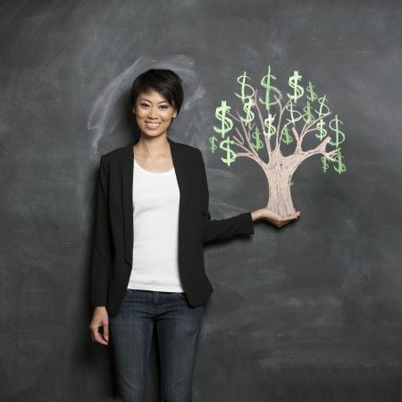 黒板に描画チョークお金ツリーの前で幸せのアジア ビジネスの女性