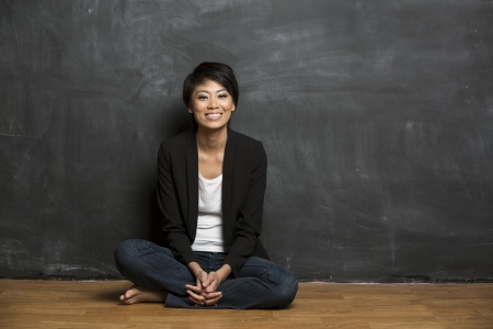 business woman standing: Happy Asian woman standing in front of a dark chalkboard  The chalk board is blank waiting for a message  Stock Photo