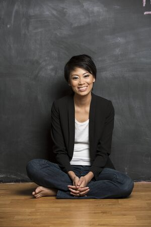 Happy Asian woman standing in front of a dark chalkboard  The chalk board is blank waiting for a message  photo