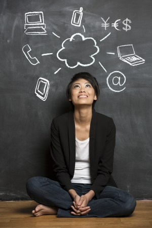 Happy Asian woman in front of Cloud computing symbols drawn on chalkboard