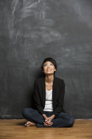 Bonne femme asiatique debout devant un tableau noir Le conseil d'administration de la craie est vierge attend un message